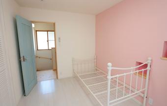 ピンク色の壁のそばにあるベッド